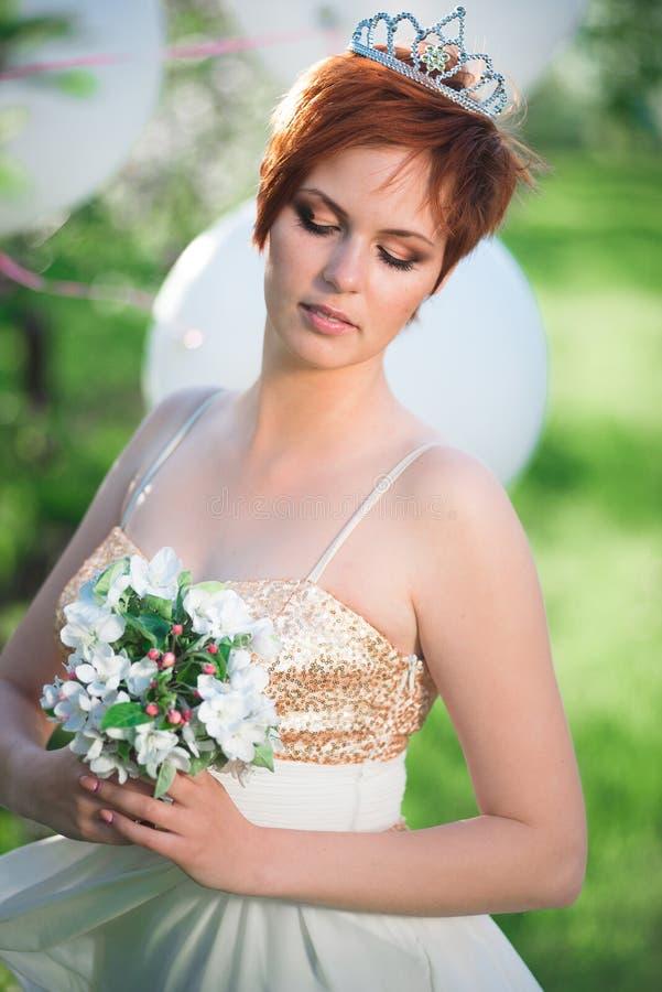 Fille sur sa tête regardant un bouquet blanc photos stock