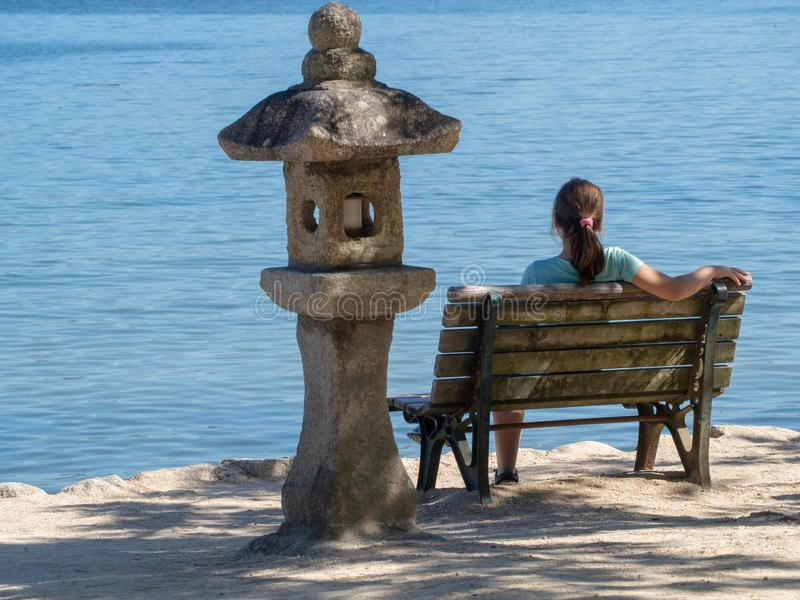 Fille sur un banc aux rivages de la mer photo stock