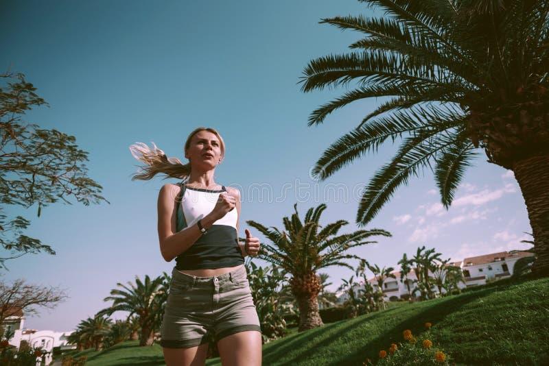 Fille sur un essai égalisant parmi des palmiers image stock