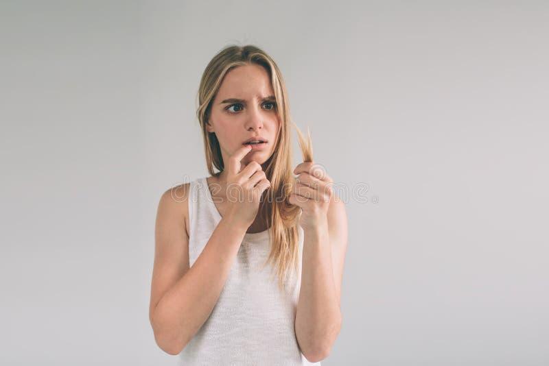 Fille sur un fond blanc avec un problème de cheveux La femme blonde utilise la chemise d'isolement sur le blanc photo stock