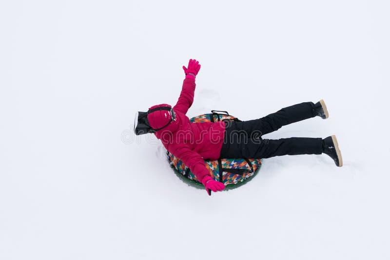Fille sur un traîneau rond à rouler dans la neige avec des verres de réalité virtuelle en hiver image stock