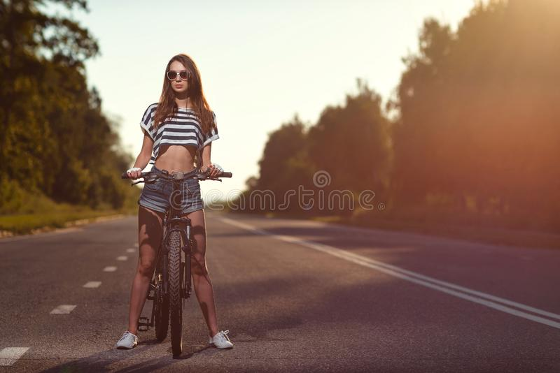 Download Fille Sur Une Bicyclette Au Coucher Du Soleil Photo stock - Image du sexy, vélo: 77162560