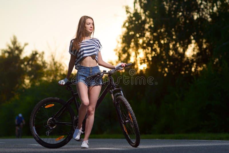 Download Fille Sur Une Bicyclette Au Coucher Du Soleil Photo stock - Image du libre, beauté: 77162588