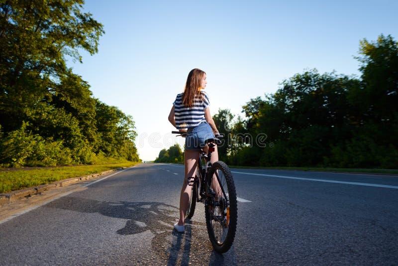 Download Fille Sur Une Bicyclette Au Coucher Du Soleil Photo stock - Image du libre, sexy: 77162692