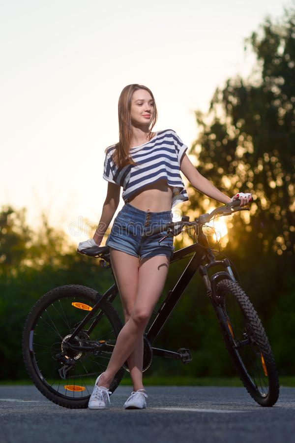 Download Fille Sur Une Bicyclette Au Coucher Du Soleil Photo stock - Image du vacances, régime: 77163362