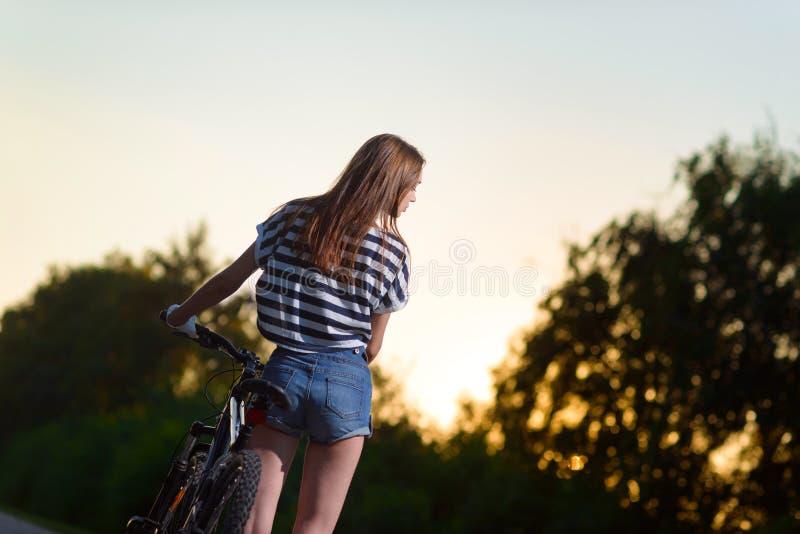 Download Fille Sur Une Bicyclette Au Coucher Du Soleil Photo stock - Image du sain, verticale: 77163472