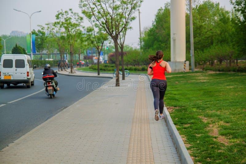 Fille sur une course de matin sur la route près d'un parc photographie stock libre de droits
