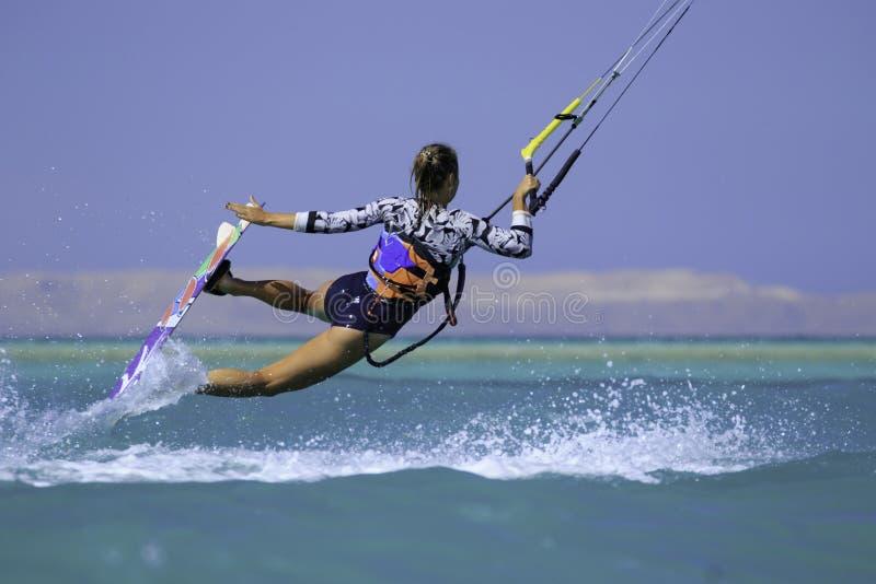 Fille surfante de cerf-volant dans le maillot de bain sexy avec le cerf-volant en ciel ? bord dans les vagues de monte de mer ble photographie stock libre de droits