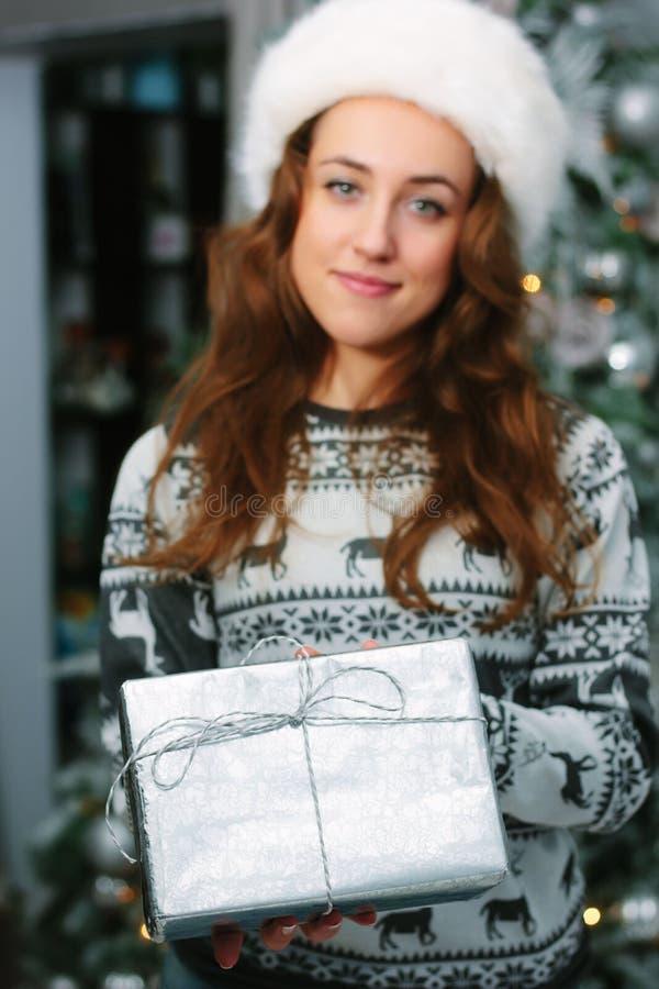 Fille te donnant un cadeau de Noël dans une boîte argentée image libre de droits