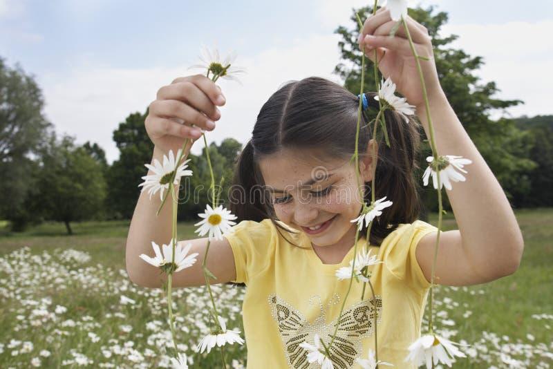 Fille tenant Daisy Chains In Meadow photo libre de droits