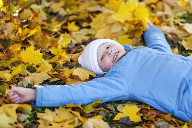 Fille tenant des feuilles d'érable photographie stock