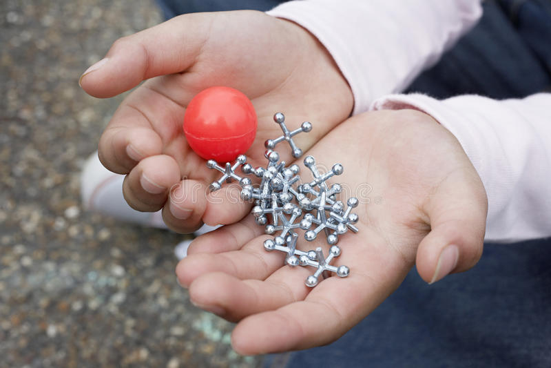 Fille tenant la boule et les crics en caoutchouc image libre de droits