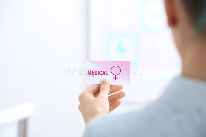 Fille tenant la carte de visite professionnelle de visite médicale à l'intérieur r photographie stock