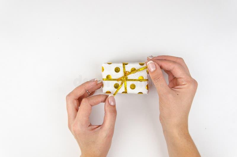 Fille tenant la petite boîte actuelle d'or dans des mains et déliant un ruban sur le fond blanc Catégoriquement, vue supérieure photo libre de droits