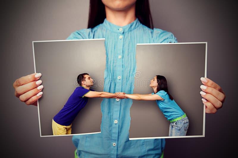 Fille tenant la photo déchirée des couples photographie stock libre de droits