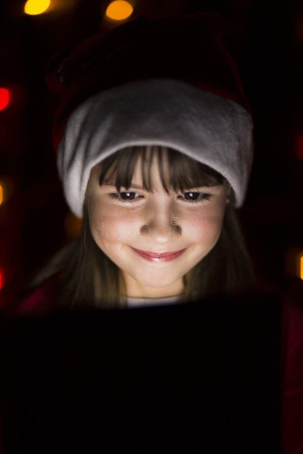Fille tenant la tablette dans le chapeau du ` s de Santa images libres de droits