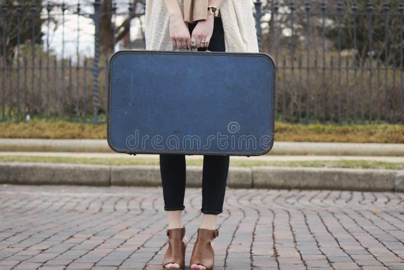 Fille tenant la valise bleue photographie stock