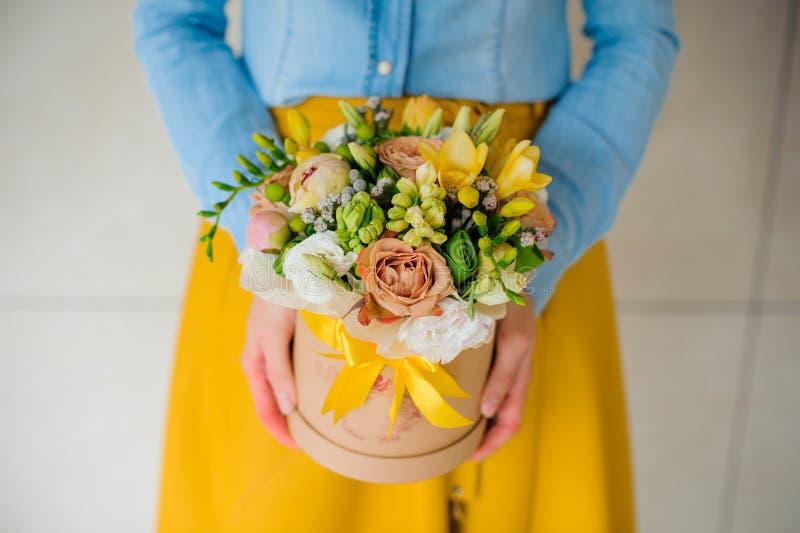 Fille tenant le beau bouquet de fleur de mélange dans la boîte ronde avec le couvercle images libres de droits