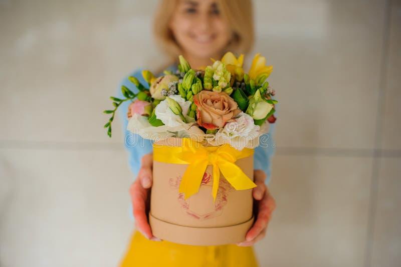 Fille tenant le beau bouquet de fleur de mélange dans la boîte ronde avec le couvercle image stock