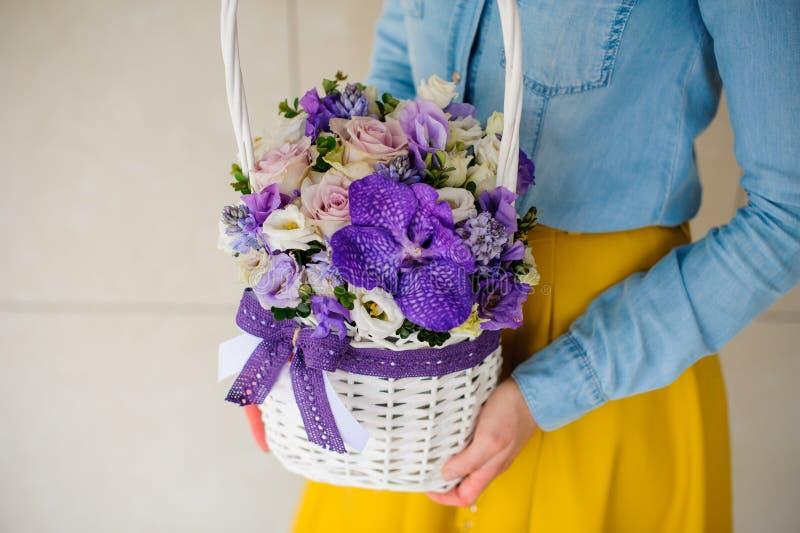 Fille tenant le beau bouquet pourpre des fleurs mélangées dans le panier photo stock