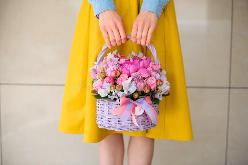 Fille tenant le beau bouquet rose des fleurs mélangées dans le panier photos stock