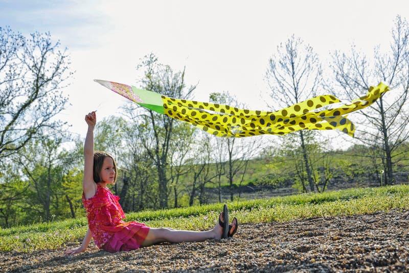 Fille tenant le cerf-volant au-dessus de la tête image stock