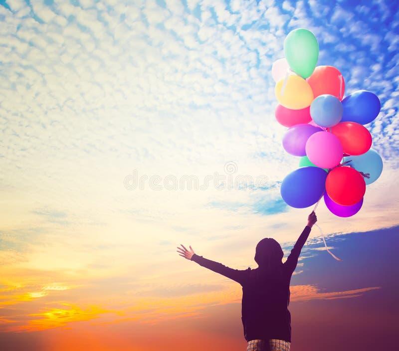 Fille tenant le groupe de ballons à air au ciel de coucher du soleil photographie stock libre de droits