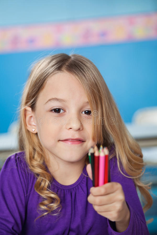 Fille tenant le groupe de crayons de couleur dans l'école maternelle images libres de droits
