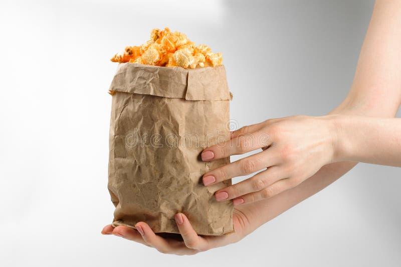 Fille tenant le maïs éclaté dans le sac de papier d'isolement sur le fond blanc photographie stock libre de droits