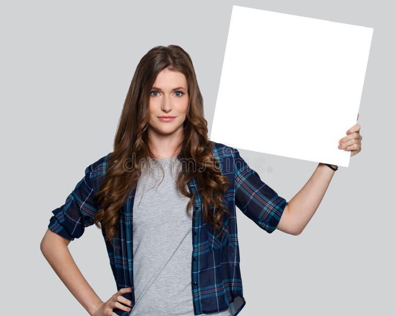Fille tenant le panneau d'affichage blanc photos stock