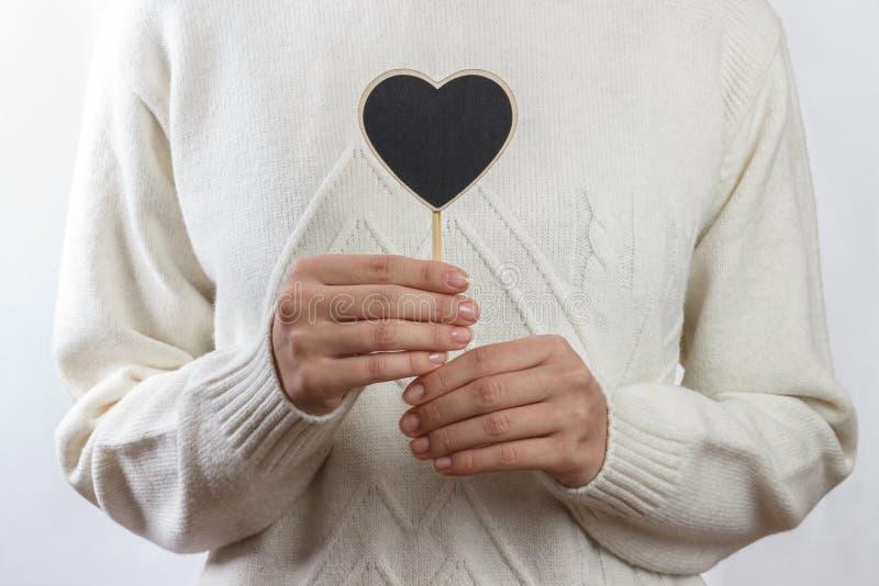 Fille tenant le panneau noir de coeur sur le fond blanc, jour de valentines images stock
