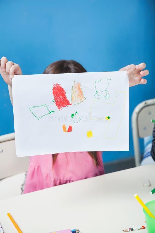 Fille tenant le papier de dessin en Front Of Face In image libre de droits