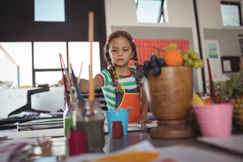 Fille tenant le pinceau tout en peignant dans la salle de classe photographie stock
