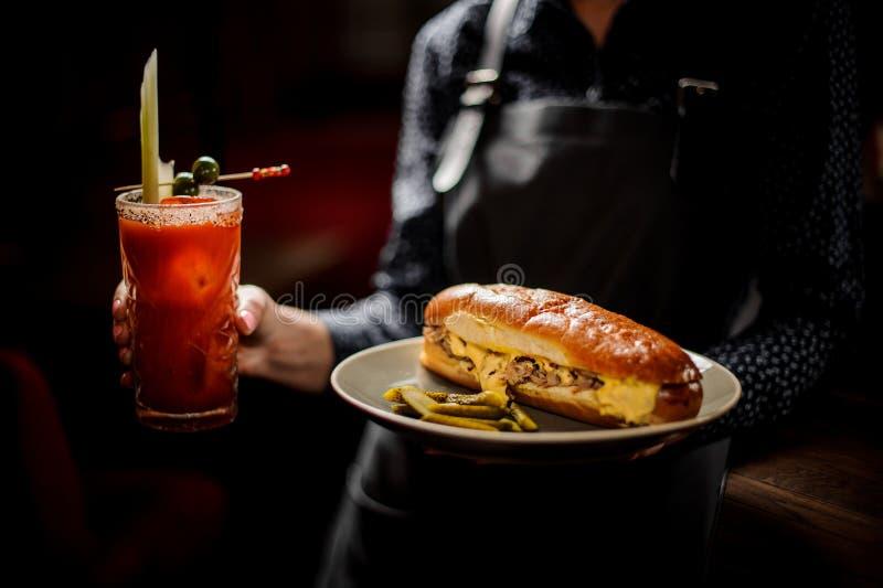 Fille tenant le plat blanc avec le sandwich savoureux à viande et le cocktail red delicious images stock
