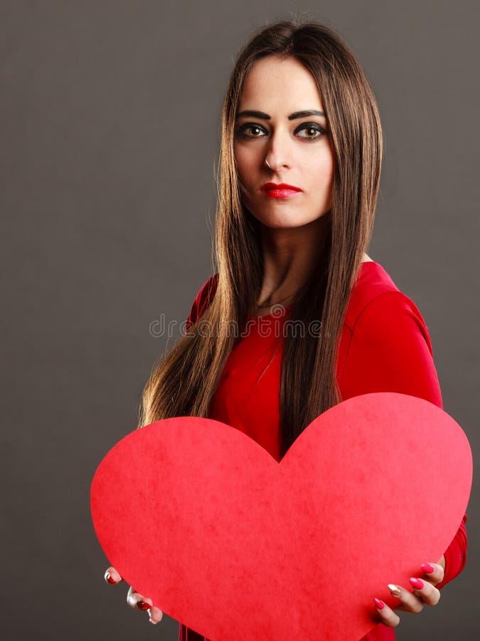 Fille tenant le signe rouge d'amour de coeur images libres de droits