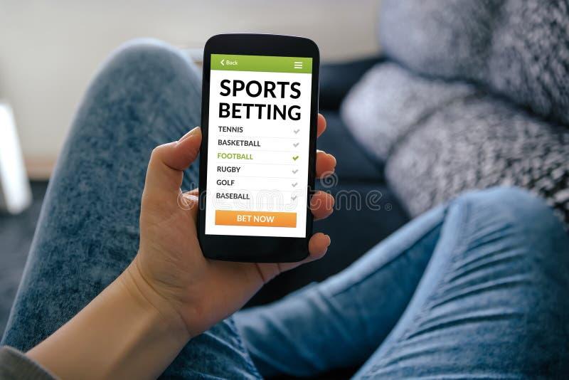 Fille tenant le téléphone intelligent avec des sports pariant le concept sur l'écran images stock