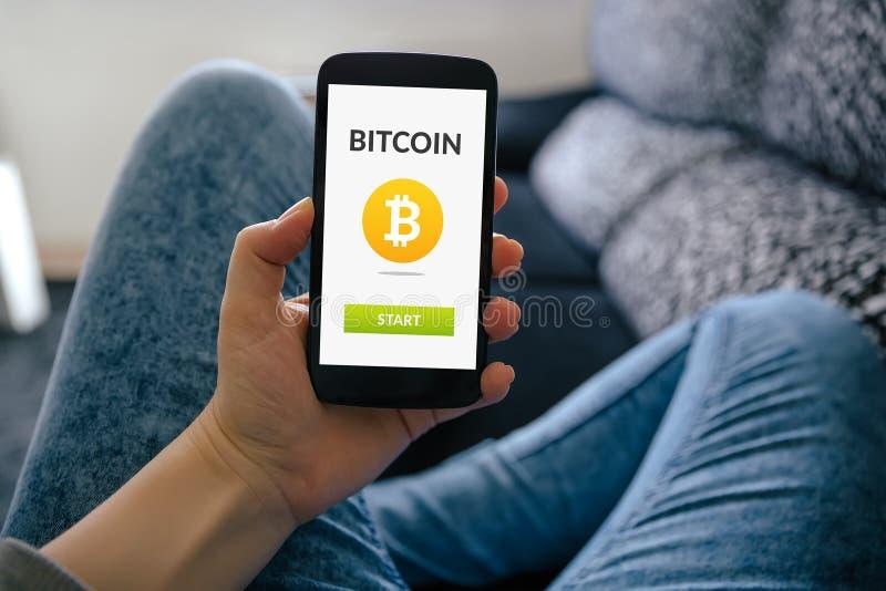 Fille tenant le téléphone intelligent avec le concept de bitcoin sur l'écran image stock