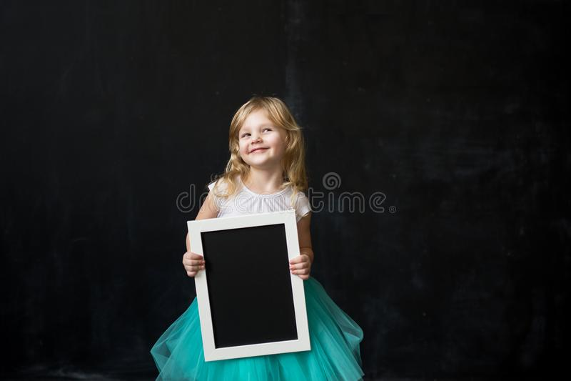 Fille tenant le tableau noir vide avec le cadre en bois image stock