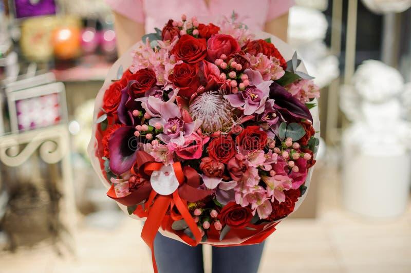 Fille tenant un beau bouquet lumineux des roses, orchidées et photos libres de droits