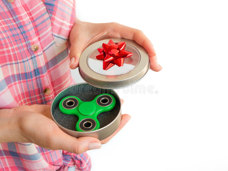 Fille tenant un jouet coloré de fileur de personne remuante de main dans un boîte-cadeau image libre de droits