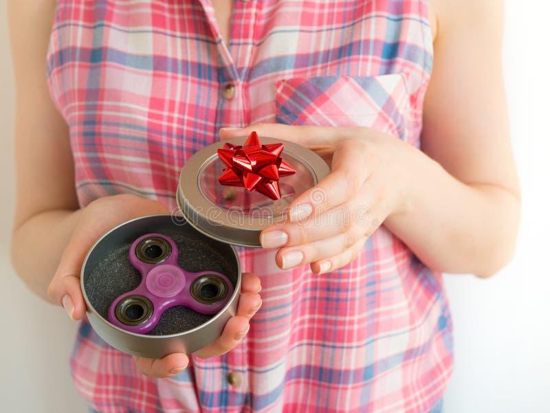 Fille tenant un jouet coloré de fileur de personne remuante de main dans un boîte-cadeau photos stock