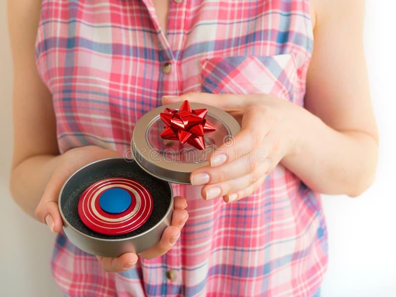 Fille tenant un jouet coloré de fileur de personne remuante de main dans un boîte-cadeau image stock