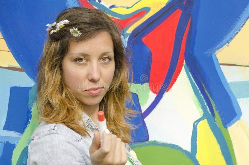 Fille tenant un rouge à lèvres contre un contexte coloré image libre de droits