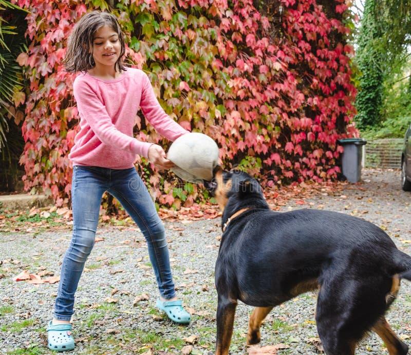 Fille tenant une boule et jouant avec le chien noir image stock