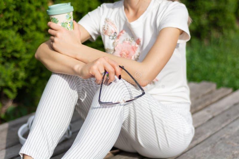 Fille tenant une tasse de café et de lunettes de soleil sur des jambes avec le pantalon rayé à la mode moderne images libres de droits