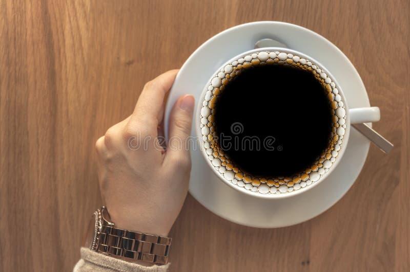 Fille tenant une tasse de café frais de brew de filtre sur une table en bois images stock
