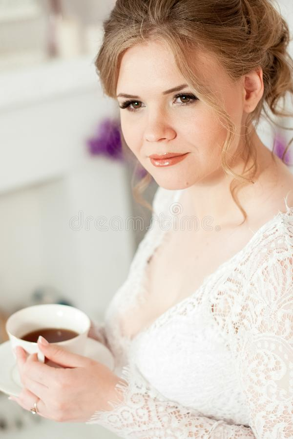 Fille tenant une tasse de caf? blanc Dans un manteau blanc Caf? dans le b?ti Le matin commence par du caf? images libres de droits