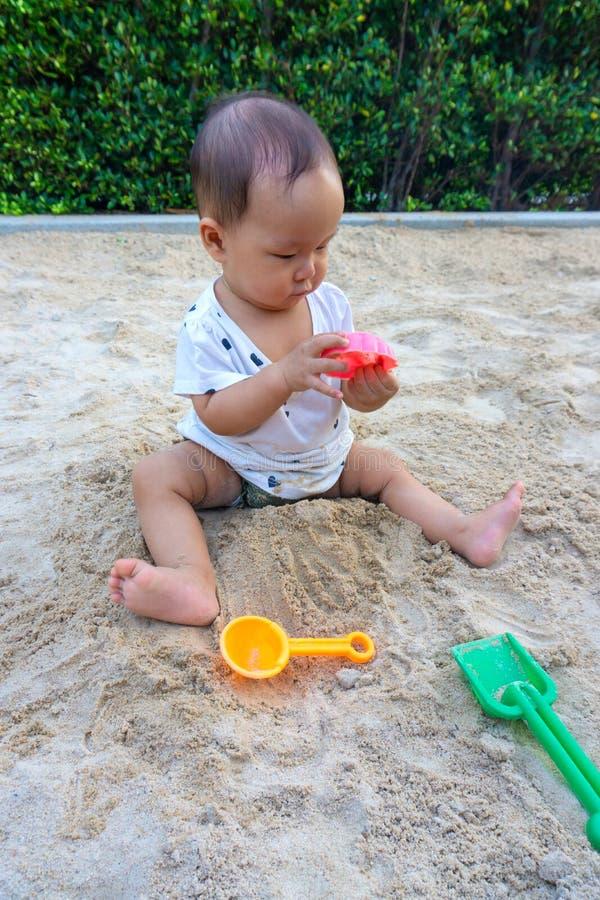 Fille thaïlandaise de bébé asiatique d'enfant en bas âge jouant avec le sable images stock