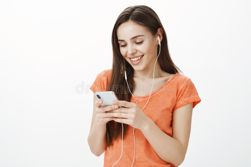 Fille timide attirante satisfaisante dans les earbuds, musique de écoute, sélectionnant la voie préférée dans le playlist de smar image stock