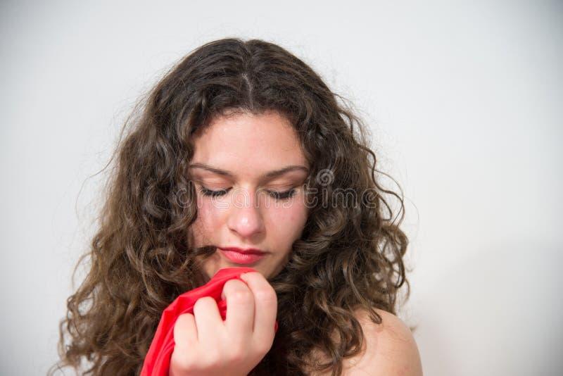 Fille très sexy avec de longs cheveux bruns onduleux, enveloppés dans une serviette rouge photo stock